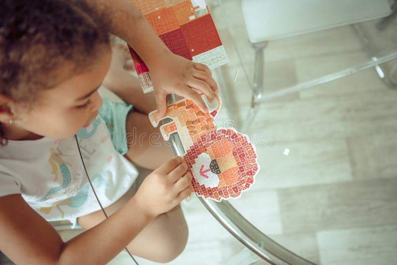 Het leuke meisje maakt applique, lijm kleurrijk huis, toepassend een kleurendocument gebruikend lijmstok terwijl binnen het doen  royalty-vrije stock afbeelding