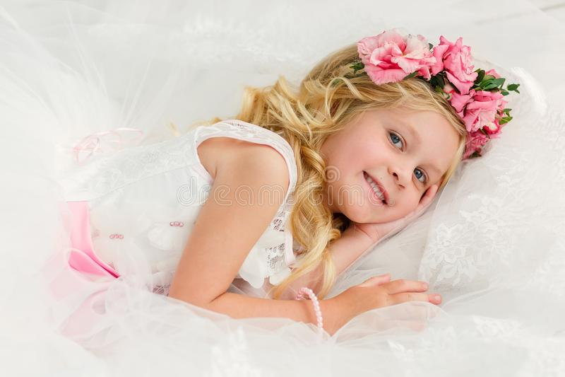 Het leuke meisje met blondehaar in een heldere studio met een kroon van bloemen ligt in een mooie witte kleding gelukkig stock afbeelding