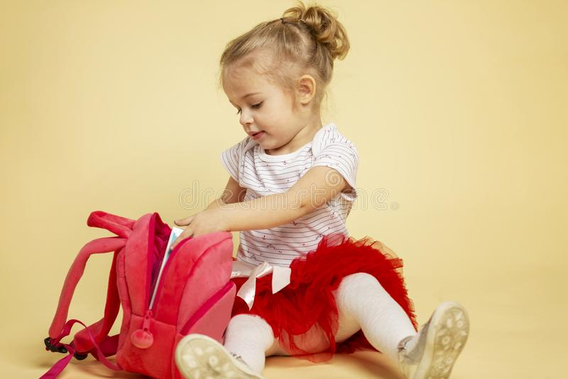 Het leuke meisje met een roze rugzak zit royalty-vrije stock afbeelding