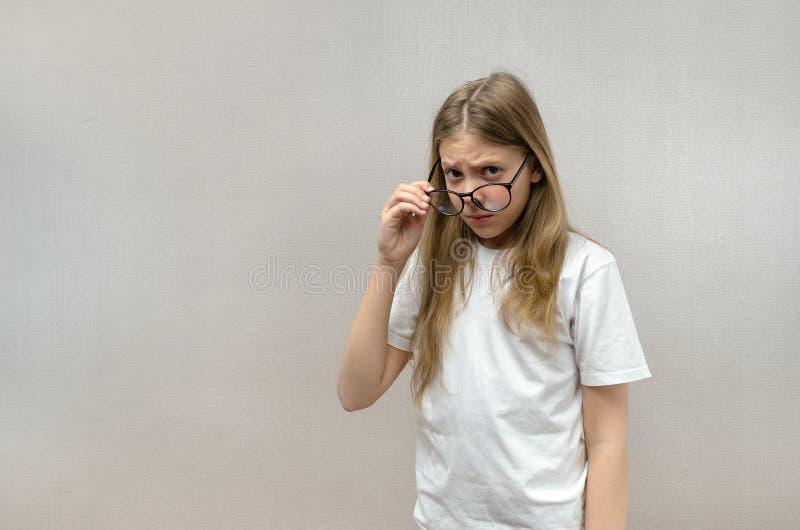 Het leuke meisje met glazen kijkt met een verdachte blik Twijfel, wantrouwen, verrassing stock afbeelding
