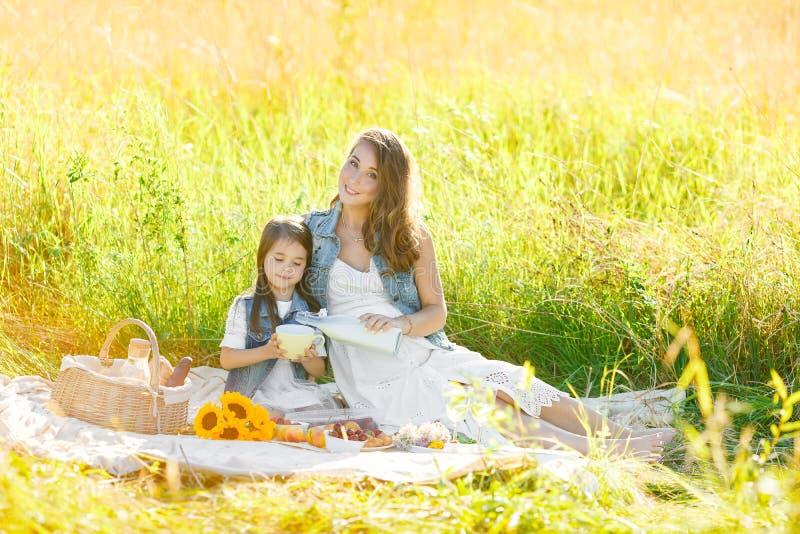 Het leuke meisje met haar zwangere moeder heeft een picknick, gelukogenblik in familielevensstijl royalty-vrije stock fotografie