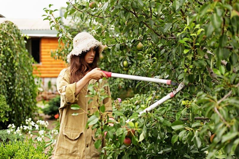 Het leuke meisje met lang haar maakt knipsel met grote tuinschaar royalty-vrije stock afbeelding