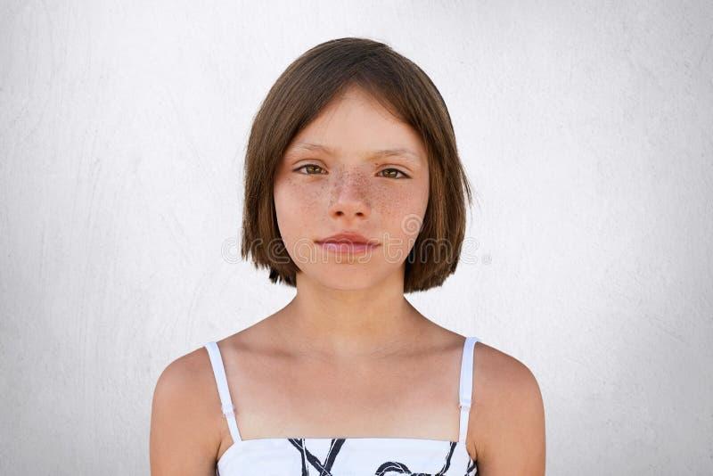 Het leuke meisje met plotseling donker bobbed haar, bruine brede glanzende ogen, zien de dunne lippen en freckled huid die witte  stock foto
