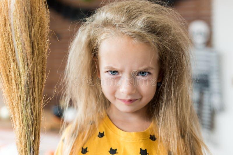 Het leuke meisje met slordig haar, die een bezem houden en omhoog gekleed als heks die zich in Halloween bevinden verfraaide woon stock foto's