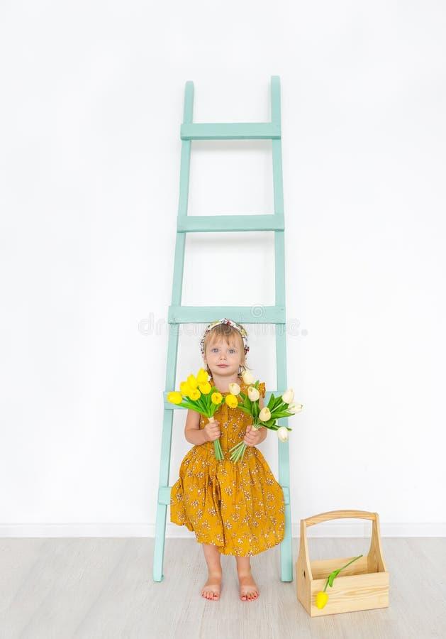 Het leuke meisje met tulpen is in een lichte de lentestudio met ladder Weinig mooie prinses royalty-vrije stock foto