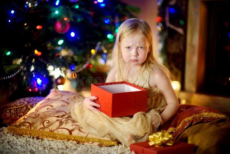 Het leuke meisje is ongelukkig met haar Kerstmisgift stock foto's