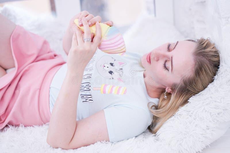 Het leuke meisje ontspant op witte vensterbank met bont alleen hoofdkussens stock foto's