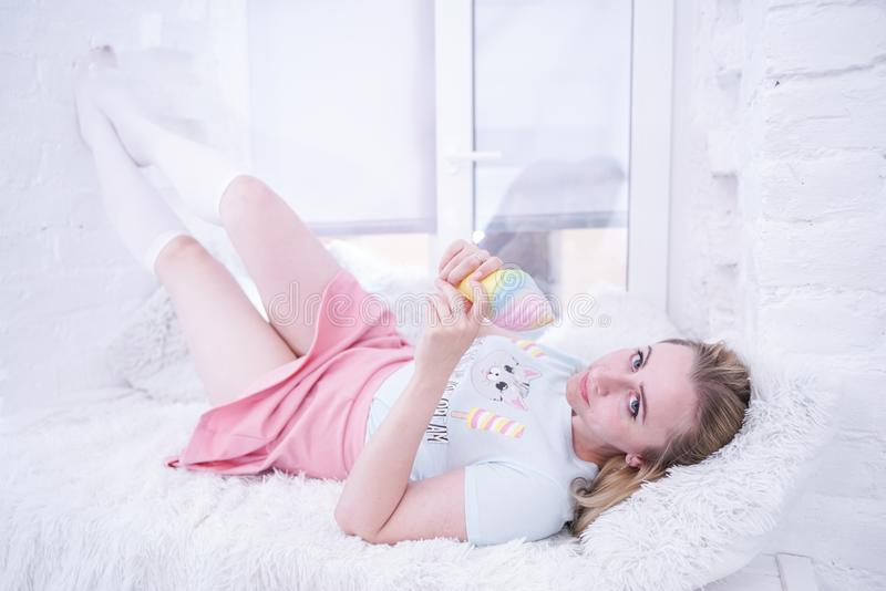 Het leuke meisje ontspant op witte vensterbank met bont alleen hoofdkussens royalty-vrije stock foto