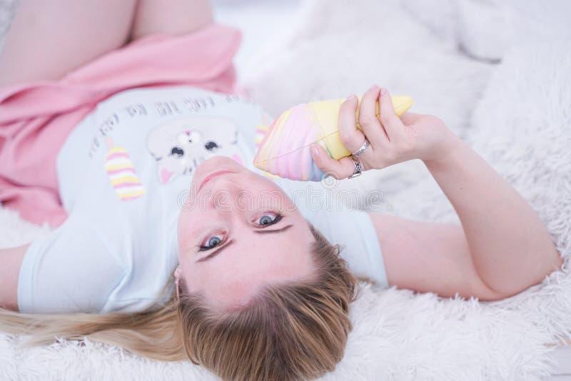 Het leuke meisje ontspant op witte vensterbank met bont alleen hoofdkussens royalty-vrije stock afbeeldingen