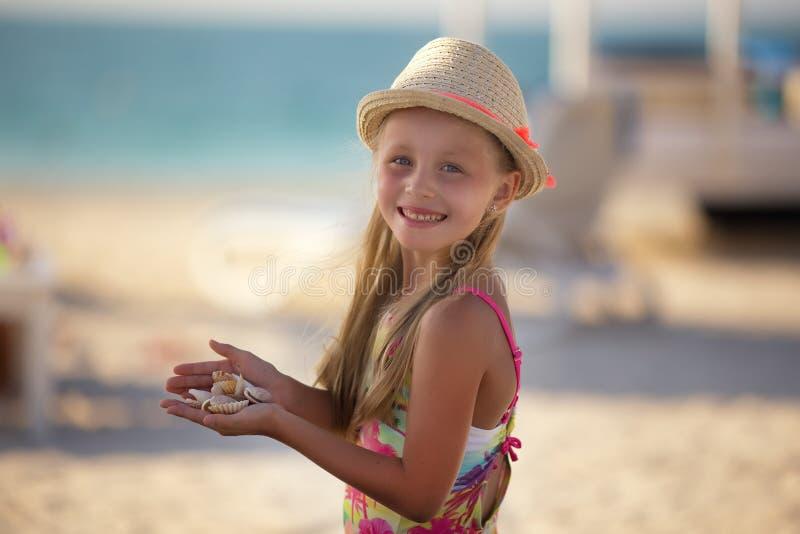 Het leuke meisje op het strand die zich in shell bevinden overhandigt royalty-vrije stock foto's