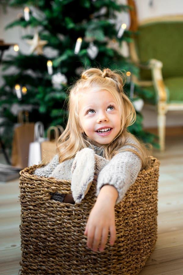 Het leuke meisje speelt met een stuk speelgoed draagt op het bed stock foto