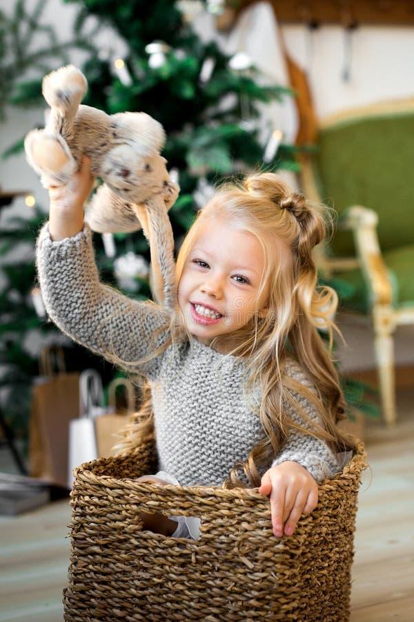 Het leuke meisje speelt met een stuk speelgoed draagt op het bed royalty-vrije stock afbeelding