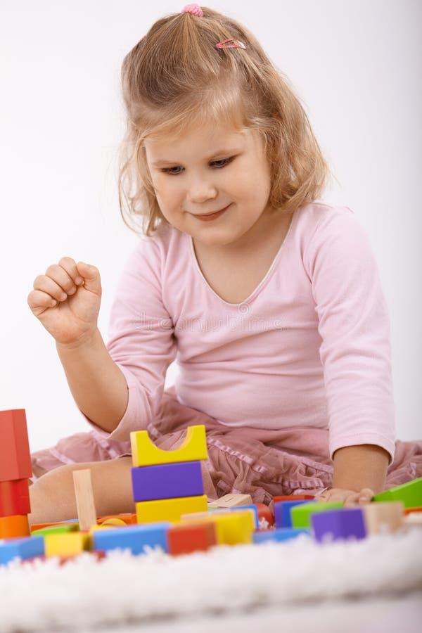 Het leuke meisje spelen bij vloer het glimlachen stock foto