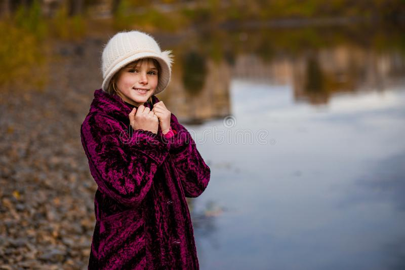 Het leuke meisje spelen in de herfstdag dichtbij meer Gelukkige kinderen die pret in de herfst hebben Het meisje kleedde zich in  royalty-vrije stock afbeelding