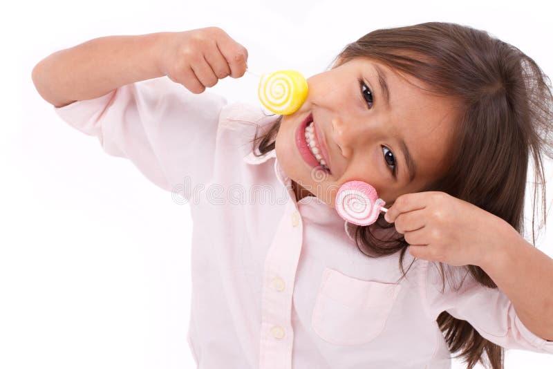 Het leuke meisje spelen, die het zoete suikergoed van de suikergelei eten royalty-vrije stock afbeeldingen