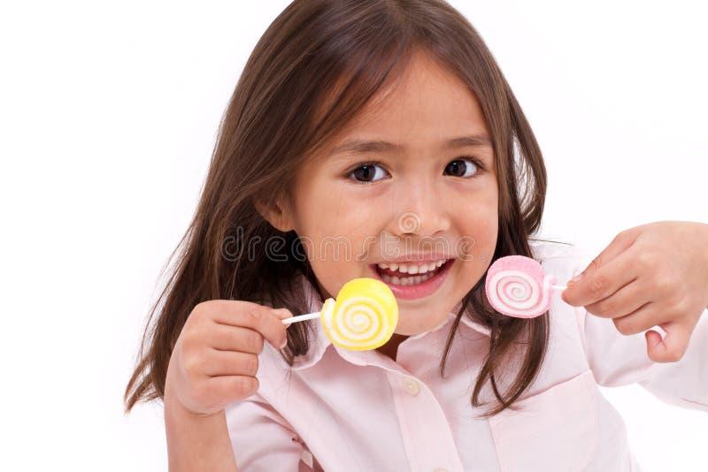 Het leuke meisje spelen, die het zoete suikergoed van de suikergelei eten stock fotografie