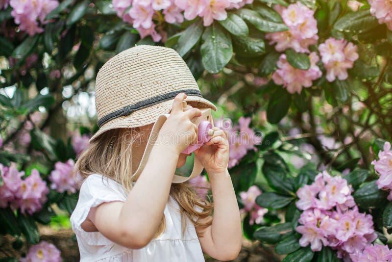 Het leuke meisje spelen met de houten camera van kinderen in het park met rododendron bloeit royalty-vrije stock afbeelding