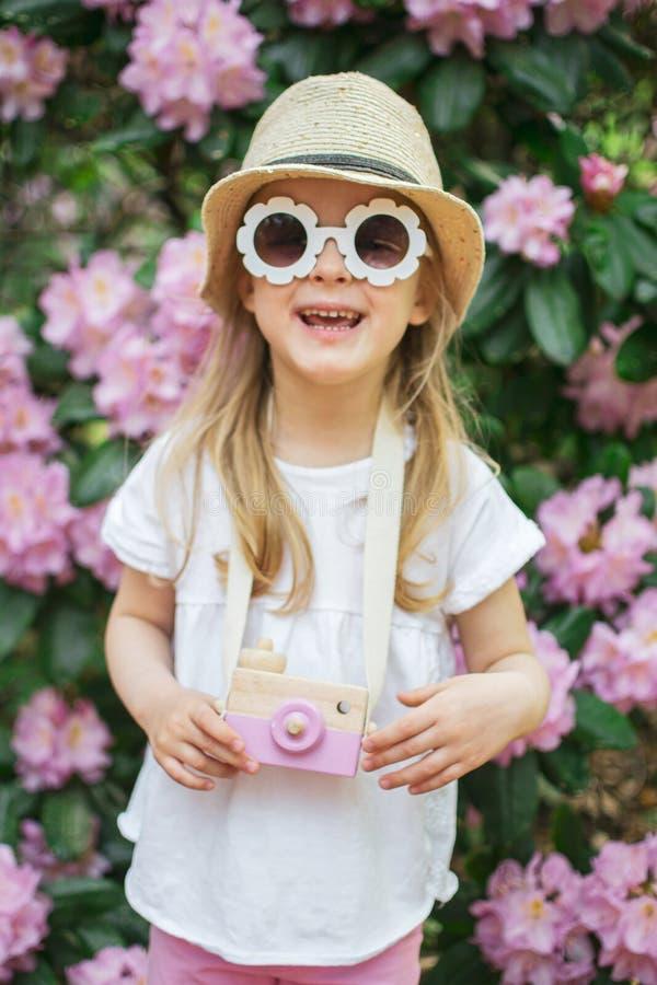 Het leuke meisje spelen met de houten camera van kinderen in het park met rododendron bloeit stock foto