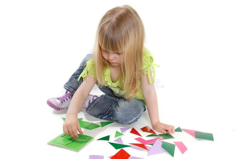 Het leuke meisje spelen met kleurrijk raadsel stock afbeeldingen