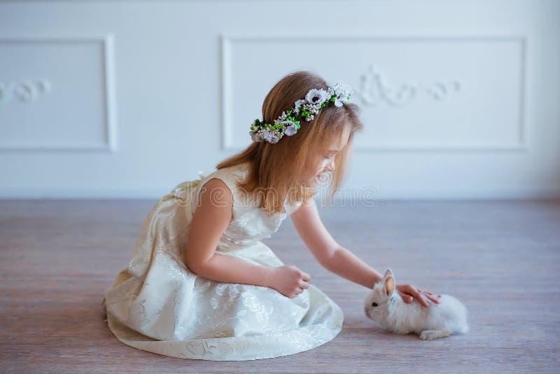 Het leuke meisje spelen met konijntje De lente en Pasen-portret van mooi kind met konijn stock foto