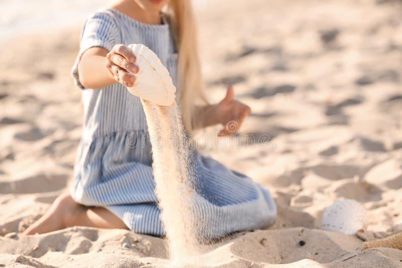 Het leuke meisje spelen met overzeese shell op strand royalty-vrije stock foto's