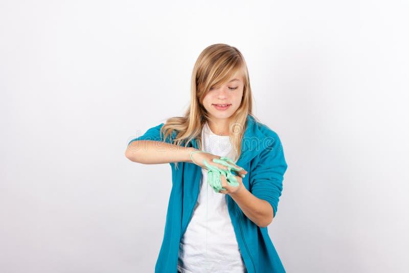 Het leuke meisje spelen met slijm kijkt als gunk stock fotografie