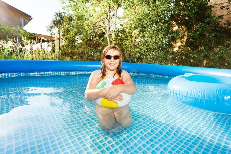 Het leuke meisje spelen met strandbal in zwembad stock fotografie