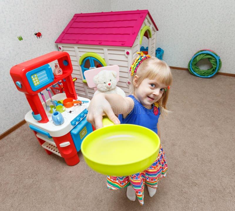 Het leuke meisje spelen met stuk speelgoed schotels in opvang royalty-vrije stock fotografie