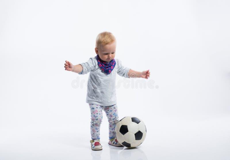 Het leuke meisje spelen met voetbalbal Het schot van de studio stock fotografie