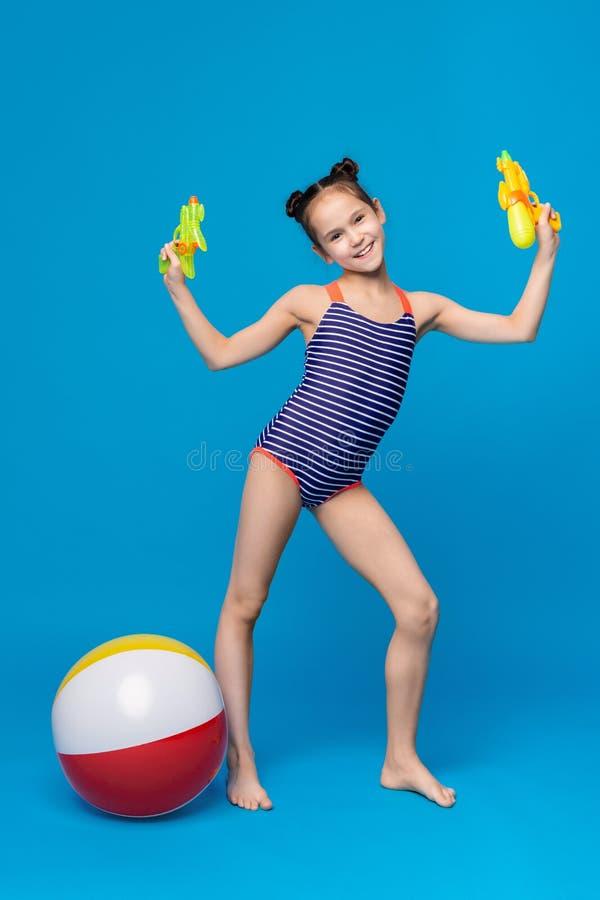 Het leuke meisje spelen met waterkanonnen en opblaasbare strandbal stock afbeelding