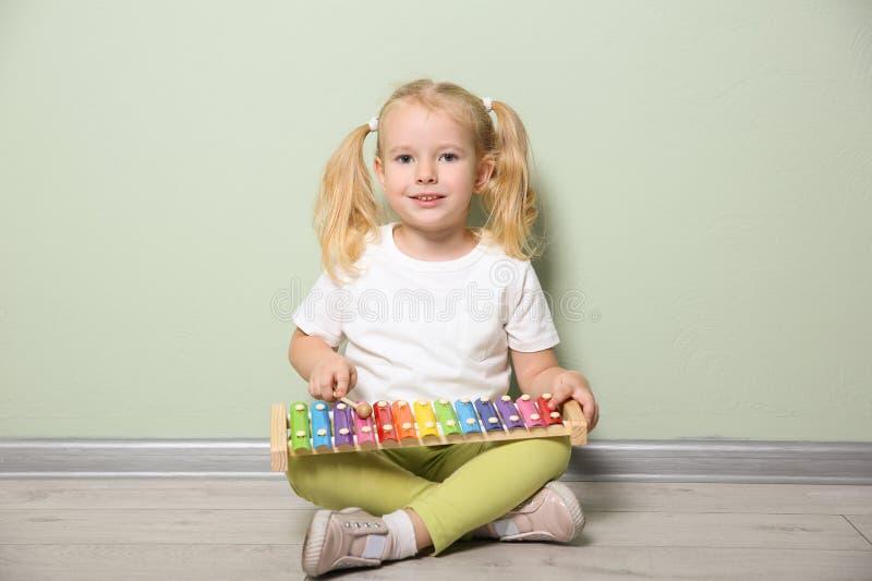 Het leuke meisje spelen met xylofoon dichtbij muur royalty-vrije stock foto
