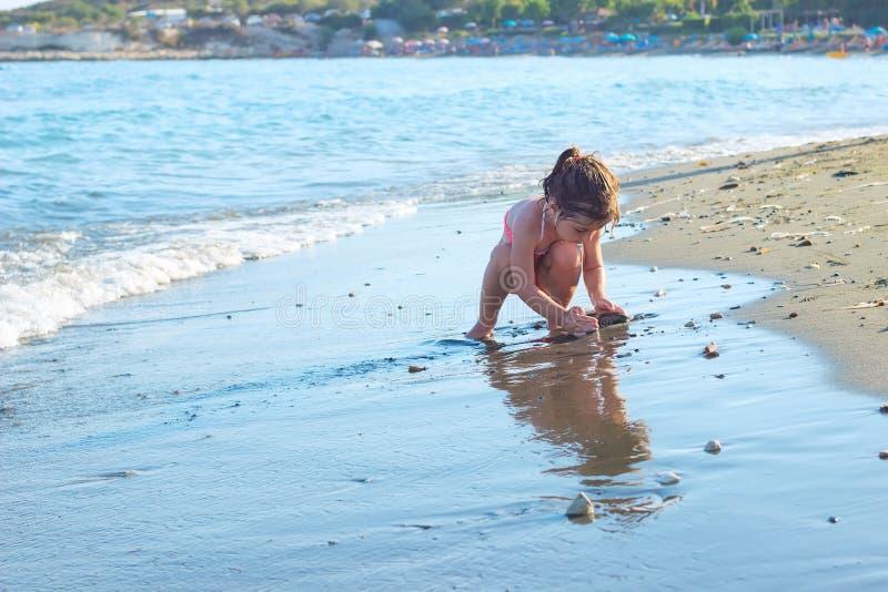 Het leuke Meisje spelen met zand door de Overzeese Golven De Zon van de zomer stock afbeelding