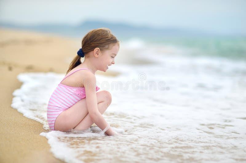 Het leuke meisje spelen op een strand stock fotografie