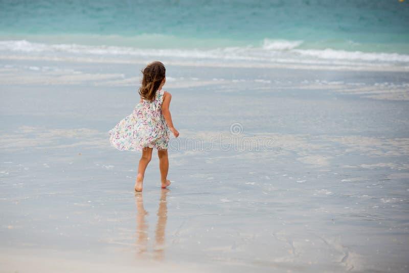 Het leuke meisje spelen op het strand in Doubai stock afbeeldingen
