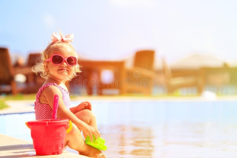 Het leuke meisje spelen in zwembad bij strand stock afbeeldingen