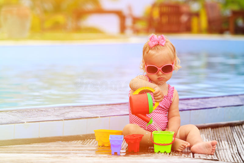 Het leuke meisje spelen in zwembad bij tropisch stock afbeeldingen