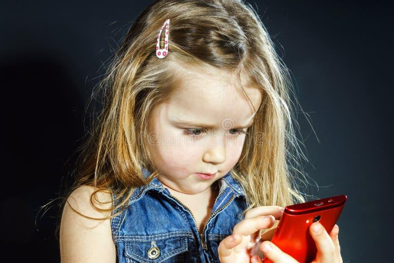 Het leuke meisje spreekt gebruikend nieuwe celtelefoon stock foto