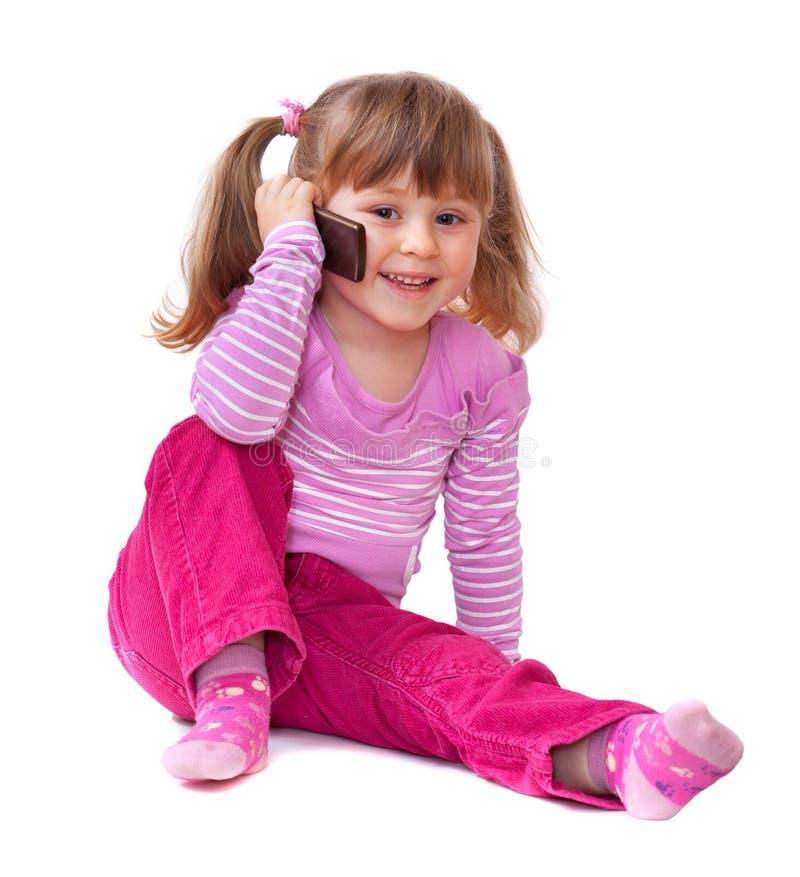 Het leuke meisje spreekt op celtelefoon stock foto's