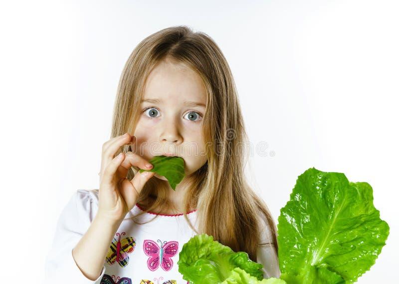 Het leuke meisje stellen met verse saladebladeren stock afbeelding