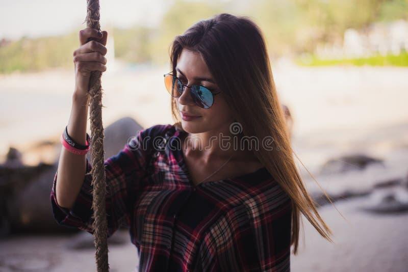 Het leuke meisje stellen op een strand Zij houdt een kabel en ver weg het kijken Perfecte foto voor een manieropslag stock afbeelding