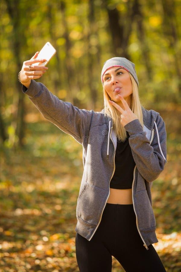 Het leuke meisje toont haar tong terwijl zij echte selfie en toont twee F stock afbeelding