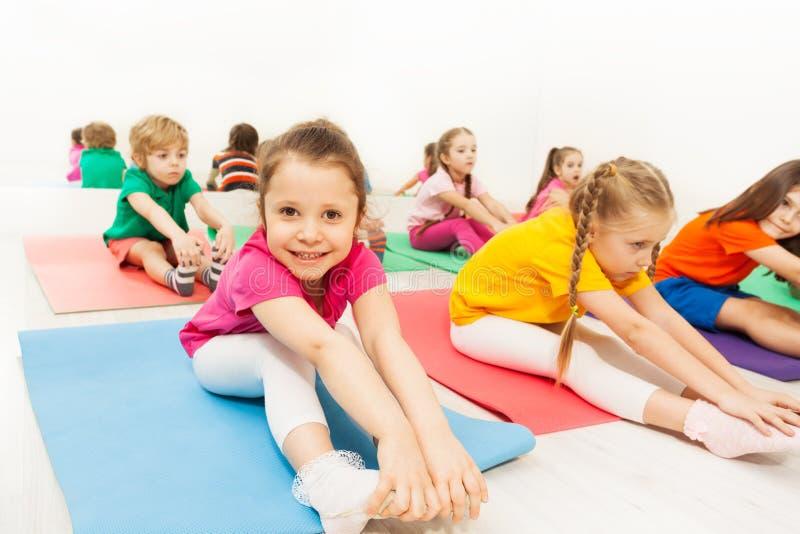 Het leuke meisje uitrekken zich op vloer in het gymnastiekcentrum stock afbeeldingen