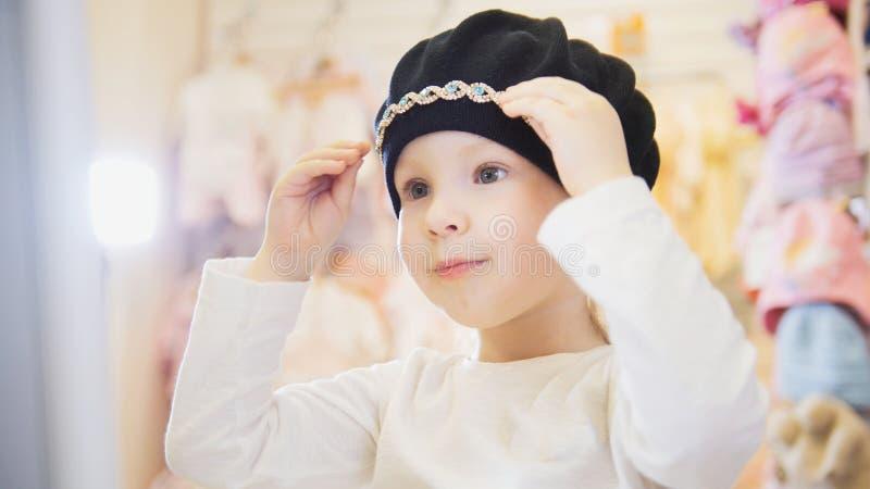 Het leuke meisje van de blondebaby in de opslag van de jonge geitjeskleding kiest leuke hoed royalty-vrije stock foto