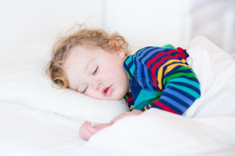 Het leuke meisje van de slaappeuter in een wit bed royalty-vrije stock foto