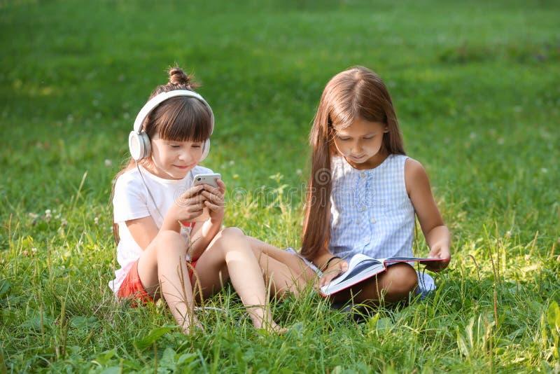 Het leuke meisjes lezen boeken en het luisteren aan muziek in park op de zomerdag royalty-vrije stock fotografie