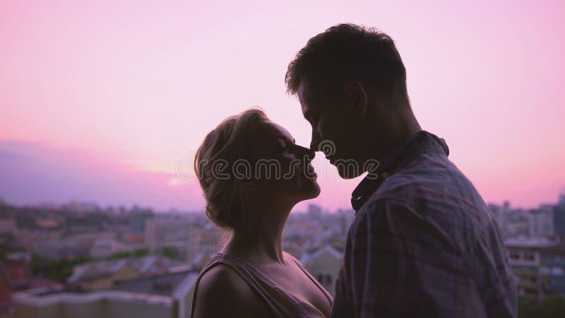 Het leuke minnaars zacht koesteren, die zich op dak, de mooie achtergrond van de zonsondergangstad bevinden stock afbeelding