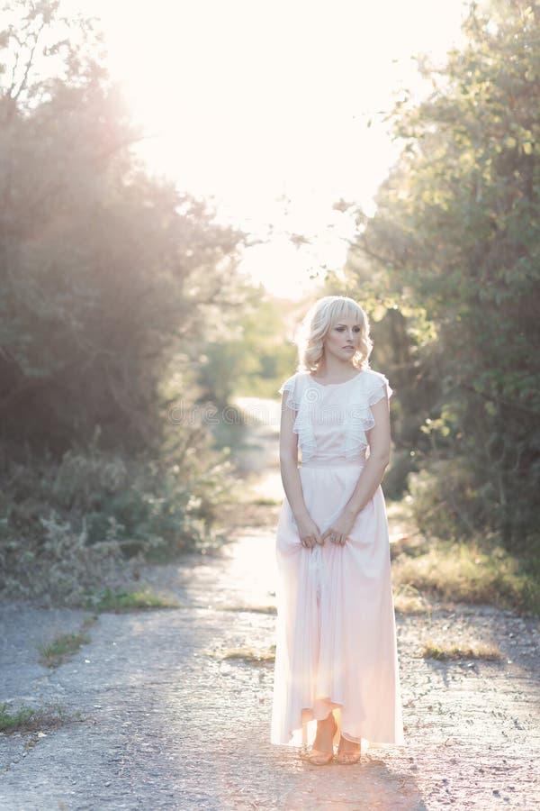 Het leuke mooie krullende haar die van het meisjesblonde in het hout in een huwelijkskleding in de zon bij zonsondergang lopen royalty-vrije stock foto