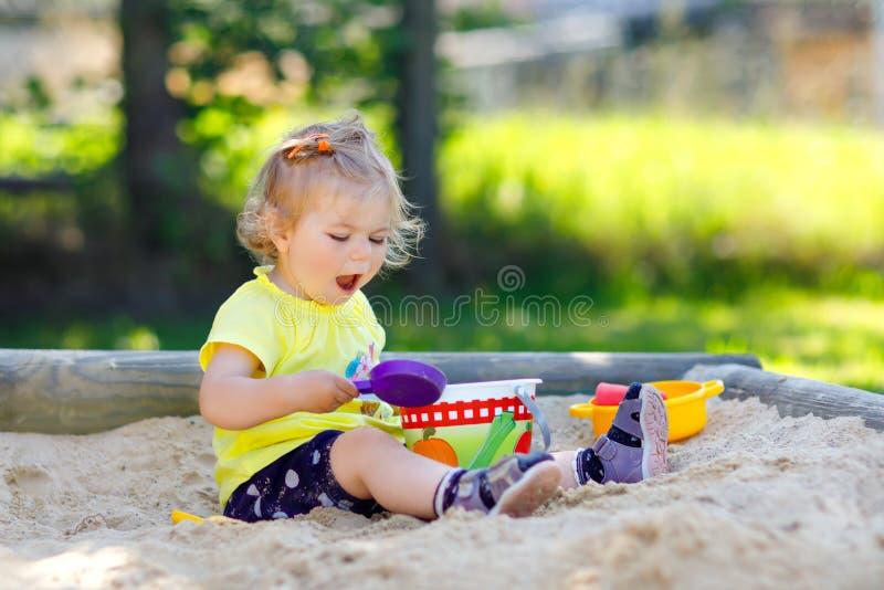 Het leuke peutermeisje spelen in zand op openluchtspeelplaats Mooie baby die pret op zonnige warme de zomer zonnige dag hebben ge stock afbeelding