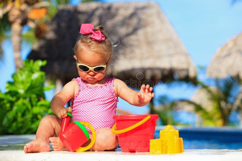 Het leuke peutermeisje spelen in zwembad stock afbeelding