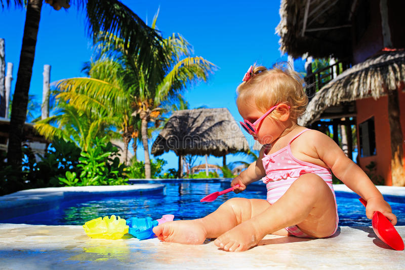 Het leuke peutermeisje spelen in zwembad bij stock foto's